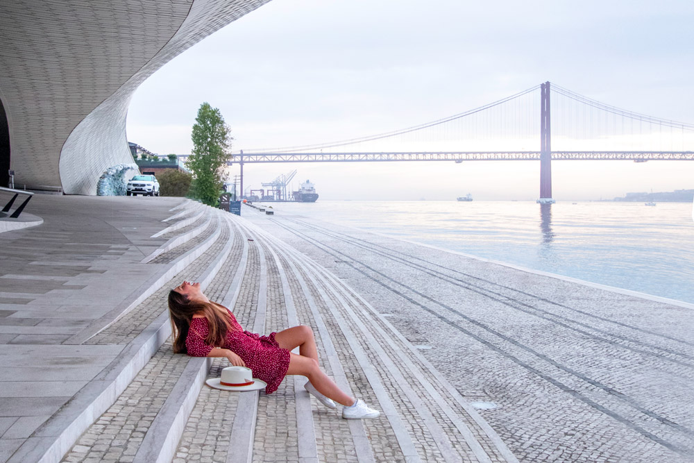 Melissa sitting under the MAAT museum, one of the best places to visit in Lisbon